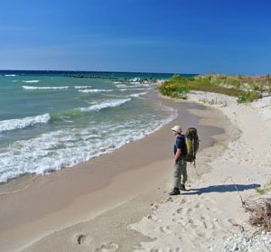A backpacker pauses along a beach on North Manitou Island.