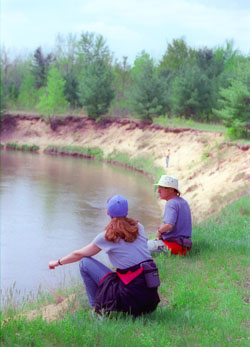 Members of Grand Traverse Hiking Club take a break at the Manistee River while following the North Country Trail.