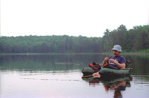 A belly boat angler changes his fly while fishing Byron Lake.
