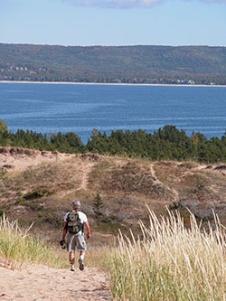 A hiker enjoys the panaromic view from a trail in Sleeping Bear Dunes National Lakeshore.