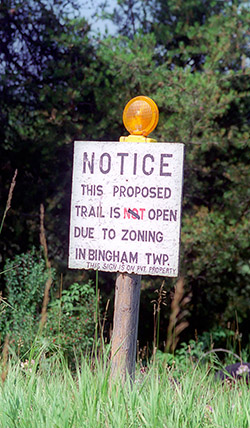 A early trail sign reflecting the opposition to the Leelanau Trail by adjacent land owners.